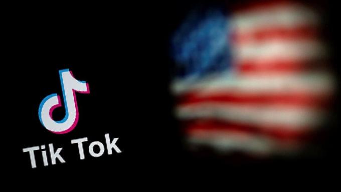 Logo TikTok và cờ Mỹ hiển thị trên hai màn hình laptop tại Bắc Kinh ngày 14/9. Ảnh: AFP.