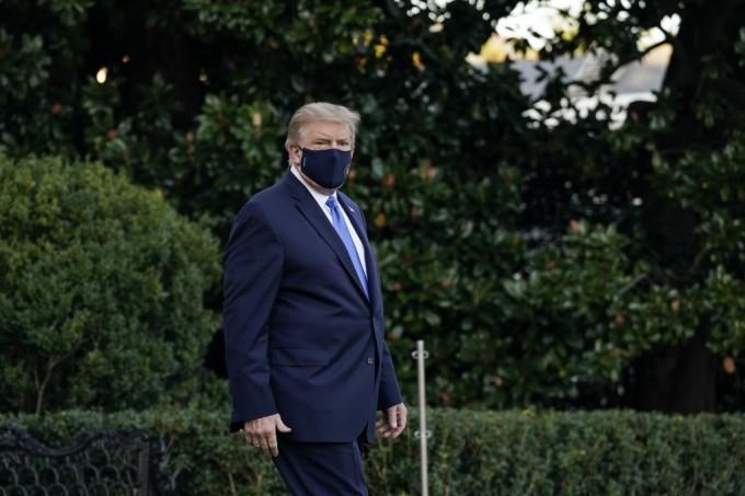 Trump đi bộ trên Bãi cỏ phía Nam ở Nhà Trắng để lên trực thăng vào viện. Ảnh: AFP.