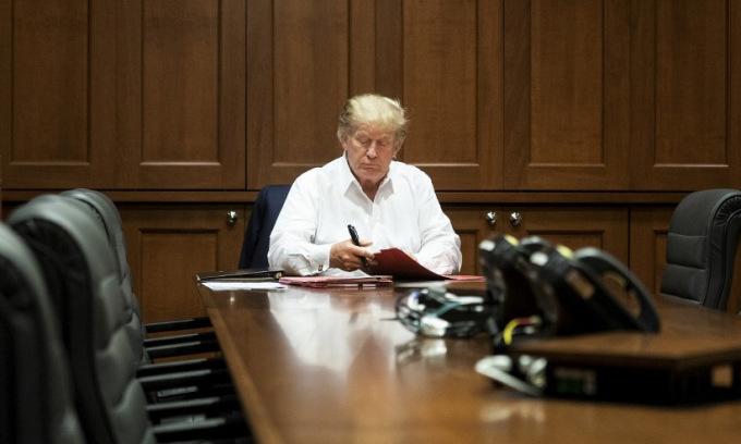 Trump ngồi tại bàn làm việc ở Trung tâm Walter Reed hôm 3/10. Ảnh: AFP.