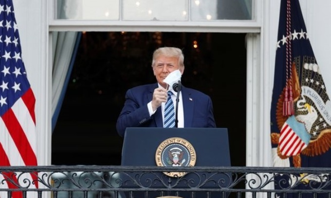 Tổng thống Trump cởi khẩu trang, chuẩn bị phát biểu trước đám đông người ủng hộ từ ban công Nhà Trắng ngày 10/10. Ảnh: Reuters.