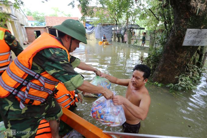 Quân đội dùng ca nô vượt lũ phát lượng thực cho người dân xã Tam Đàn, huyện Phú Ninh sáng 12/10. Ảnh: Đắc Thành.