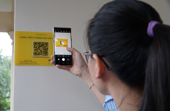 Chị Như Loan (người dân huyện Đất Đỏ) dùng điện thoại quét mã QR tại Công viên tượng đài Võ Thị Sáu, trưa 14/11. Ảnh: Trường Hà.