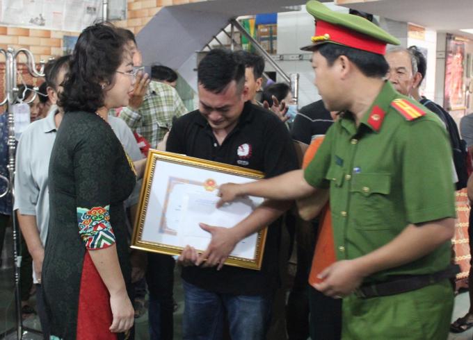Bà Vy Vũ Hồng Thảo tặng bằng khen cho gia đình anh Quang tối 15/10. Ảnh: Thái Hà