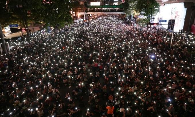 Người biểu tình Thái Lan giơ đèn pin điện thoại trên đường phố Bangkok hôm 15/10. Ảnh: AFP.