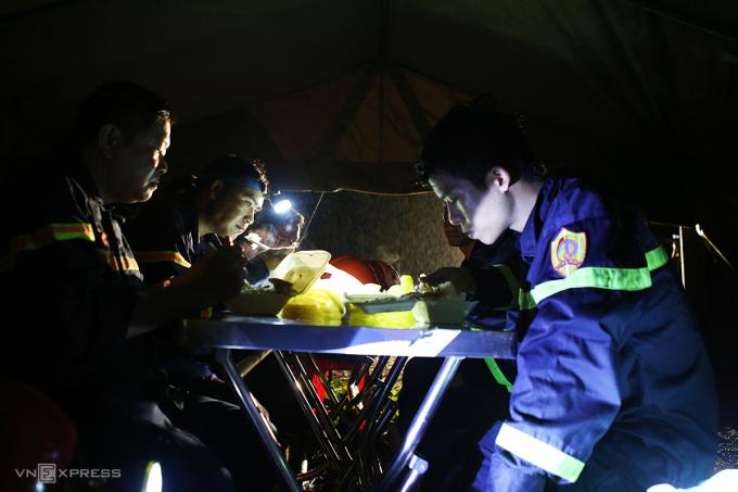 Lính cứu hộ soi đèn pin ăn bữa tối. Ảnh: Nguyễn Hải.