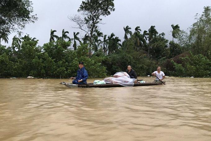 Người dân xã Hương Toàn (thị xã Hương Trà) chèo thuyền giữa nước lũ nhận mì tôm, nhu yếu phẩm cứu trợ. Ảnh: Hoàng Táo