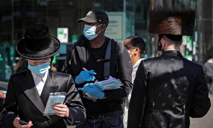Nhân viên Cơ quan Truy vết và Xét nghiệm nCoV của thành phố New York phát khẩu trang cho những người thuộc cộng đồng Do Thái Chính thống ở khu Borough Park, Brooklyn, ngày 9/10. Ảnh: Reuters.