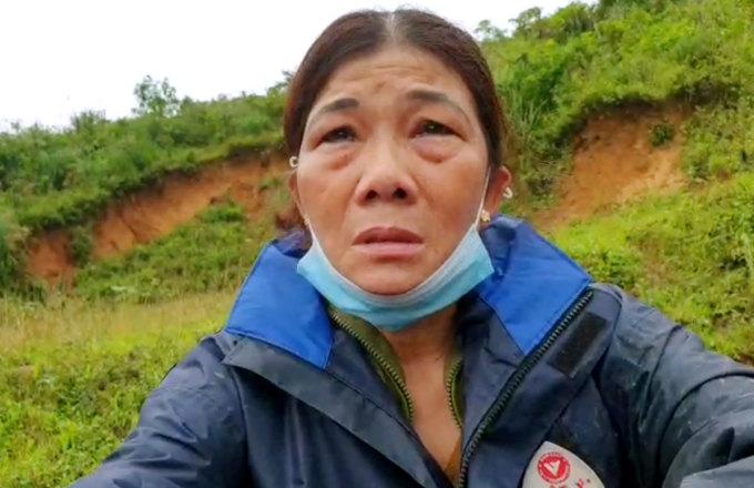 Bà Lê Hà Thị Dung ngồi bệt bên đường khóc, xem nhà chức trách tìm thi thể con rể. Ảnh: Táo Hoàng