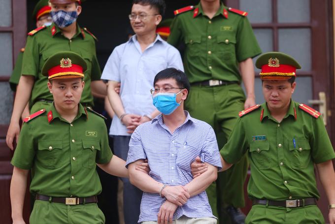 Bị cáo Khương Ngọc Chất (đeo khẩu trang) và Nguyễn Quang Vinh rời toà sáng 14/5. Ảnh: Phạm Dự.