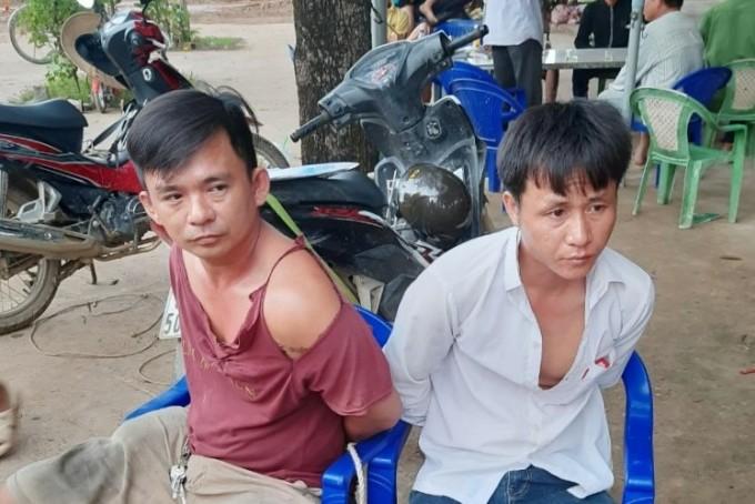 Tài xế Hoàng Xuân Vinh (đỏ) cùng Nguyễn Công Võ bị tạm giữ sáng nay để điều tra. Ảnh: Đức Huynh.