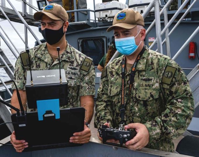 Binh sĩ đứng trên một tàu chiến để điều khiển UAV tiếp cận tàu ngầm. Ảnh: US Navy.