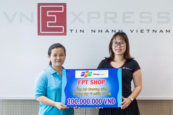 Bà Trần Thu Hà - Giám đốc kinh doanh vùng của FPT Retail (góc phải) trao tiền hỗ trợ đồng bào miền Trung cho bà Nguyễn Thị Hải - VnExpress. Ảnh: Thành Nguyễn.