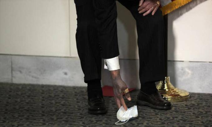 Thượng nghị sĩ Mitch McConnell để lộ bàn tay phải sẫm màu với ngón cái được băng bó khi cúi nhặt khẩu trang hôm 21/10. Ảnh: AP.
