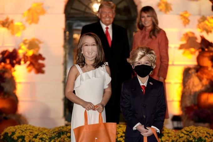 Trump và Melania chụp ảnh cùng hai em bé hoá trang thành vợ chồng ông. Ảnh: Reuters.