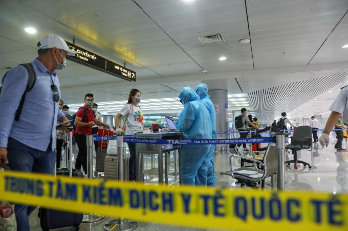 Nhân viên Trung tâm Kiểm dịch Y tế Quốc tế TP HCM (Sở Y tế) giám sát thân nhiệt người nhập cảnh tại sân bay Tân Sơn Nhất, ngày 24/3. Ảnh:Hữu Khoa.