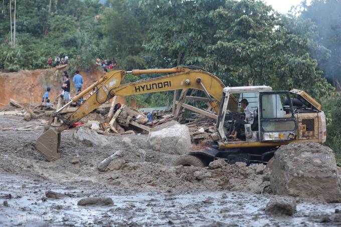 Máy xúc san gạt đất đá tại hiện trường lở núi thôn 1, xã Trà Leng. Ảnh: Ngọc Thành