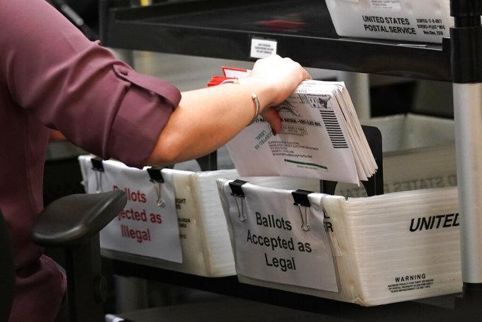 Một nhân viên bầu cử phân loại phiếu bầu qua thư ở Doral, Florida ngày 26/10. Ảnh: AP.