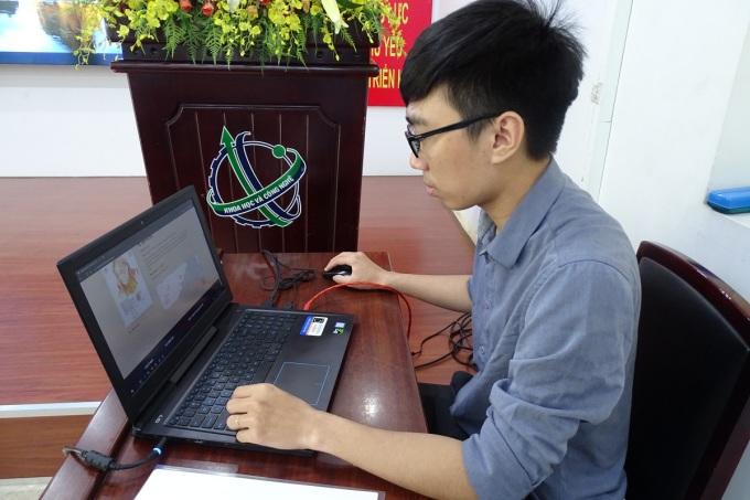 Bạn trẻ xem chân dung mẹ Việt Nam Anh Hùng và tìm hiểu thông tin trên website. Ảnh: Hà An.