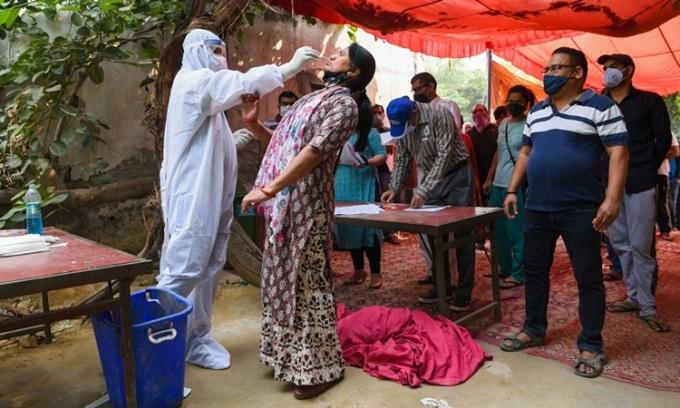 Nhân viên y tế lấy mẫu xét nghiệm cho người dân ở Ghaziabad, Ấn Độ hôm 29/10. Ảnh: AFP.