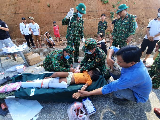Bộ đội sơ cứu cho bé Hà My, con gái của chị Hồ Thị Hà tại đầu quốc lộ 40B, chiều 29/10. Ảnh: Đắc Thành