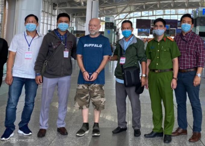 Wade Astle (áo xanh, còng tay) bị cảnh sát áp giải ra sân bay Nội Bài hôm 23/10.Ảnh: Quyết Nguyễn