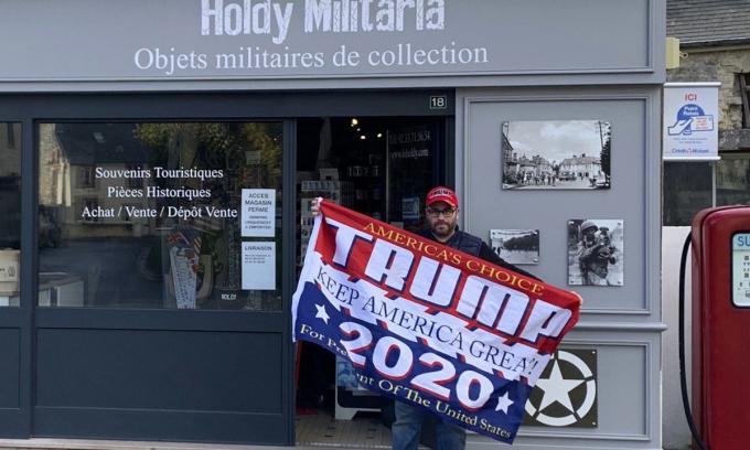 Philippe Tanne, người ủng hộ Trump, đứng trước cửa hàng ở thị trấn Sainte Marie du Mont ở Normandy, Pháp hôm 3/11. Ảnh: AP.