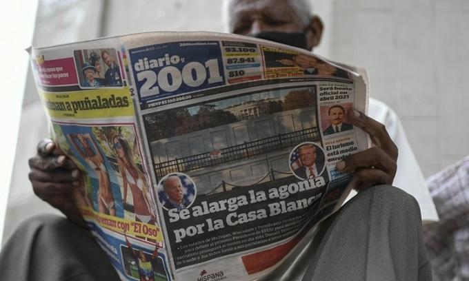 Người đàn ông đọc tờ báo Diario 2001 có tiêu đề tiếng Tây Ban Nha Cơn hấp hối nối dài với Nhà Trắng tại quầy báo ở Caracas, Venezuela hôm 4/11. Ảnh: AP.