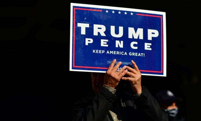 Một người ủng hộ giơ bảng có logo chiến dịch tranh cử của Tổng thống Trump tại Philadelphia, Pennsylvania hôm 6/11. Ảnh: Reuters.