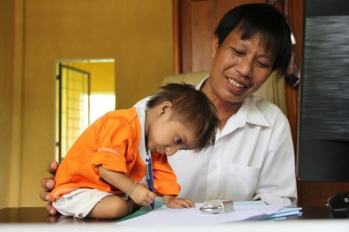 Thầy Cương dạy cậu bé tí hon tập viết, năm 2016. Ảnh: Thạch Thảo.