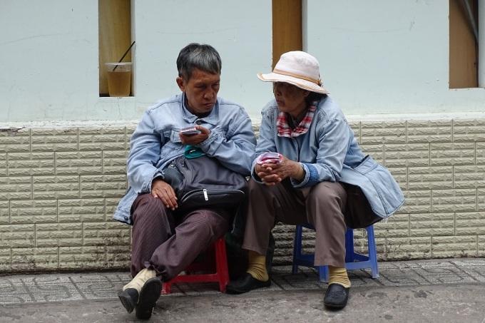 Hai người bán vé số ở quận Gò Vấp mặc áo khoác bò để chống lạnh, sáng 11/11. Ảnh: Hà An.