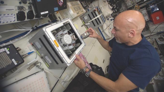Phi hành gia Luca Parmitano đặt lò phản ứng sinh học vào một máy ly tâm trên ISS. Ảnh: ESA.