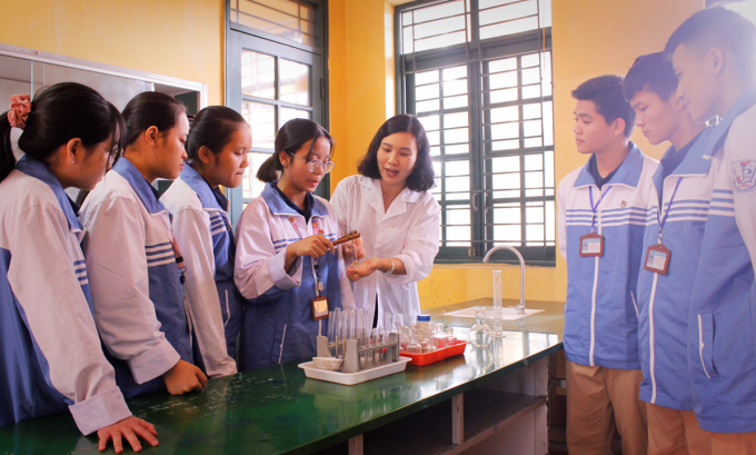 Cô Nguyệt hướng dẫn cho học sinh làm thực hành Hóa học. Ảnh: Nhân vật cung cấp