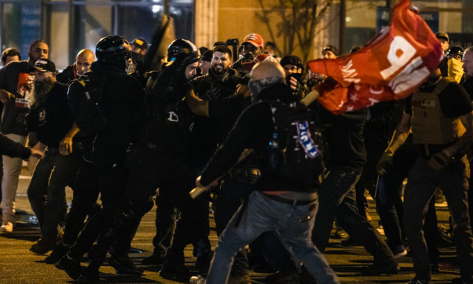 Cảnh sát ngăn cản cuộc đụng độ giữa những người ủng hộ và phản đối Tổng thống Donald Trump tại thủ đô Washington, Mỹ. hôm 14/11. Ảnh: AFP.