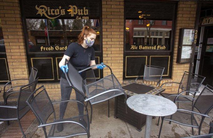 Nhân viên sắp xếp bàn ghế ngồi ngoài trời tại quán rượu Rico ở Pullman, Washington, hôm 16/11. Ảnh: AP.