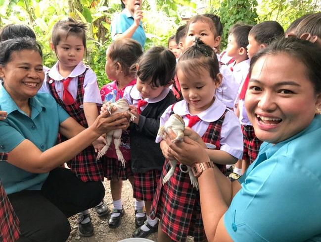 Các thầy cô và cả nhân viên của trại ếch đều có mặt để hỗ trợ, khích lệ các em thử chạm vào con ếch.