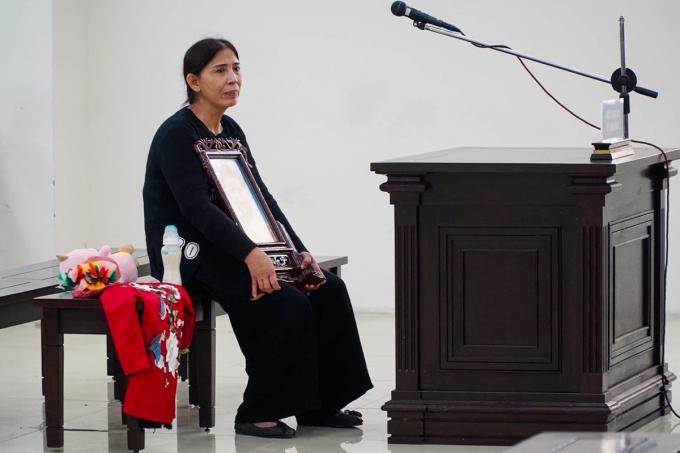 Bà Vũ Thị Dự mang theo di ảnh và đồ chơi, quần áo của bé Minh tới phiên toà. Ảnh: Danh Lam