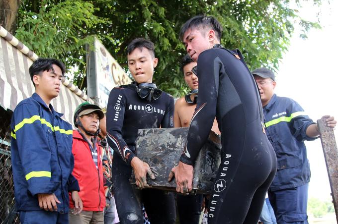 Két sắt nặng hơn 40 kg được hai cảnh sát khiên lên bờ sau khi tìm được dưới rạch Đĩa, huyện Nhà Bè. Ảnh: Đình Văn.