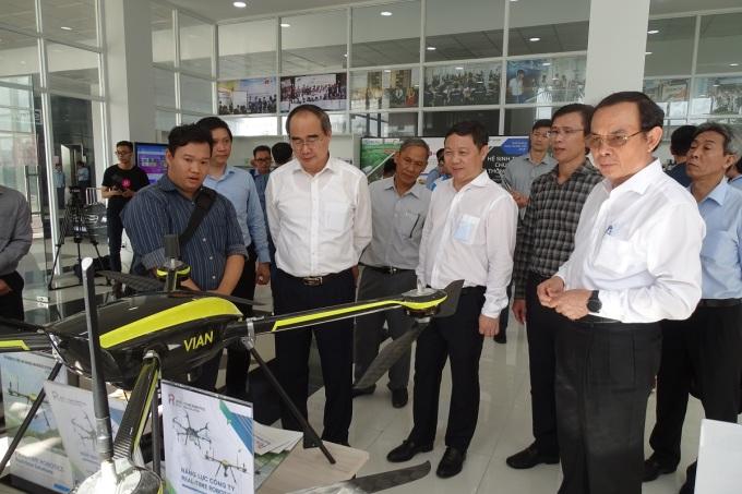 Bí thư Thành ủy TP HCM Nguyễn Văn Nên (ngoài cùng bên phải), ông Nguyễn Thiện Nhân (thứ 2 từ trái sang) tham quan các gian hàng công nghệ tại Vườn ươm doanh nghiệp Khu công nghệ cao. Ảnh: Hà An.