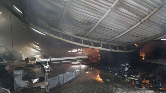 Mái tôn của một xưởng gỗ đổ sập trong đám cháy. Ảnh: Phạm Tuấn