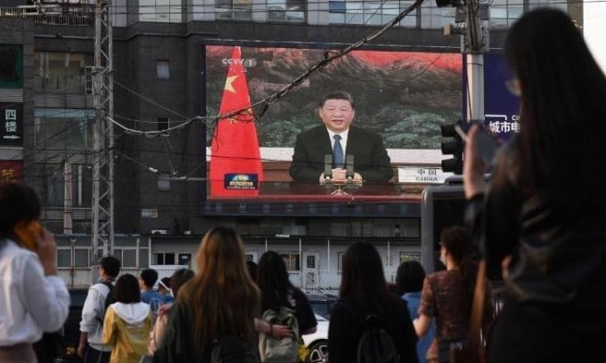 Người dân Trung Quốc quan sát Chủ tịch Tập Cận Bình phát biểu trước Đại hội đồng Y tế Thế giới trên một con phố ở Bắc Kinh hôm 18/5. Ảnh: AFP
