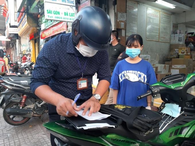 Nữ nhân viên bãi xe trên đường phạm ngũ lão bị lập biên bản xử phạt vì không mang khẩu trang. Ảnh: Ninh Sự.