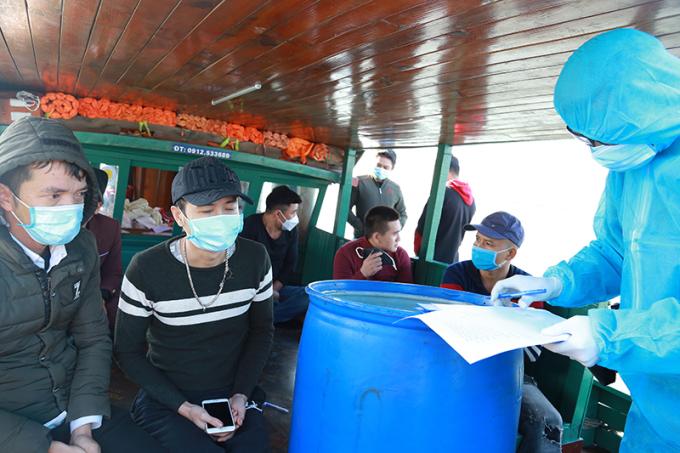 Lực lượng chức năng lấy lời khai 8 khách nam trốn cách ly y tế trên đò gỗ. Ảnh: BĐBP