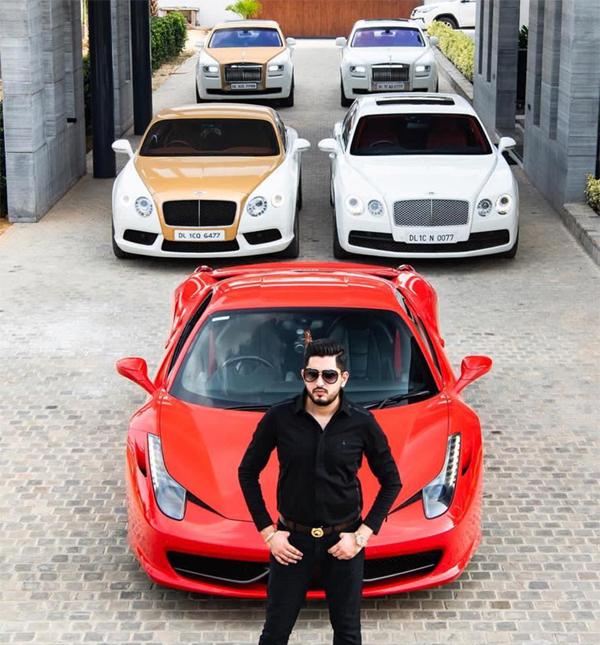 Chủ nhân bộ sưu tập đứng trước một chiếc Ferrari màu đỏ, phía sau bên trái là một chiếc Bentley và một Rolls-Royce cùng tông màu.
