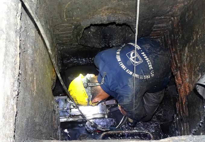 Công nhân đưa robot vào miệng cống thoát nước trên quốc lộ 13 (quận Bình Thạnh). Ảnh: Hà An.