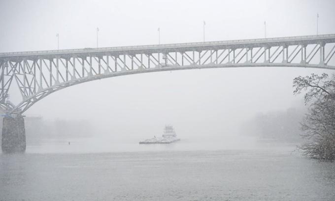 Một chiếc tàu kéo di chuyển dưới chân cầu ở thành phố Pittsburgh, bang Pennsylvania trong trận bão tuyết ngày 16/12. Ảnh: AP.