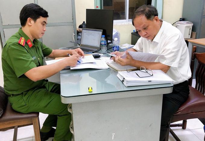 Ông Tất Thành Cang (phải) sau khi nhận quyết định khởi tố bị can, bắt tạm giam, chiều 16/12. Ảnh: Công an cung cấp.