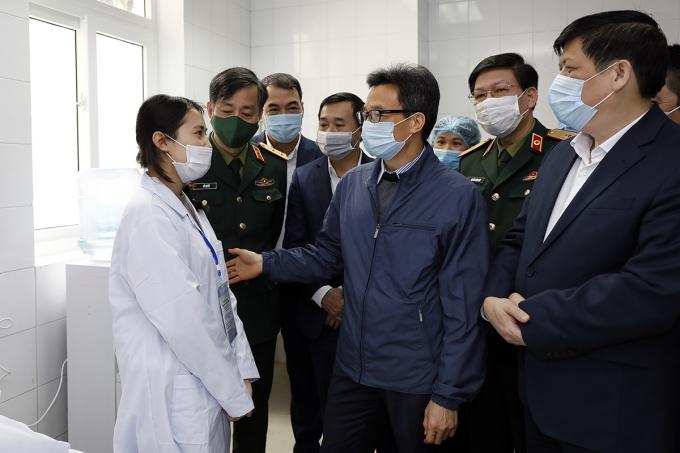 Phó thủ tướng Vũ Đức Đam động viên một trong ba tình nguyện viên đầu tiên tiêm thử nghiệm vaccine Covid-19 do Việt Nam sản xuất. Ảnh: Đình Nam