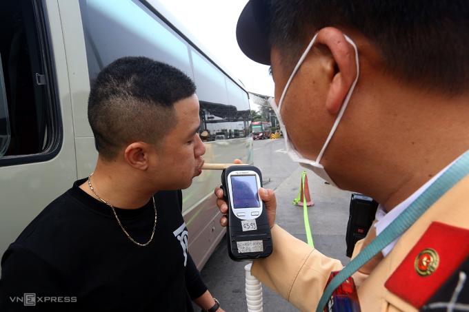 Cảnh sát kiểm tra nồng độ cồn bằng ống thổi tre với một tài xế xe khách chiều 22/12 trên cao tốc Pháp Vân-Cầu Giẽ. Ảnh: Bá Đô
