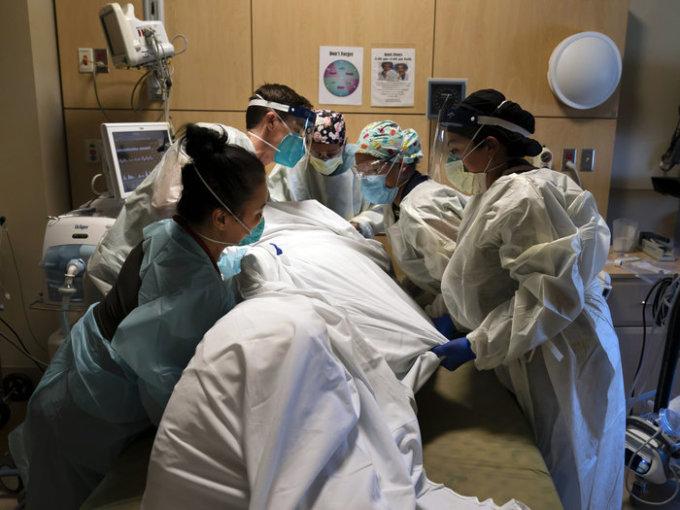 Các nhân viên y tế giúp đặt một bệnh nhân Covid-19 nằm úp tại Trung tâm Y tế Providence Holy Cross ở Los Angeles hôm 19/11. Ảnh: AP.