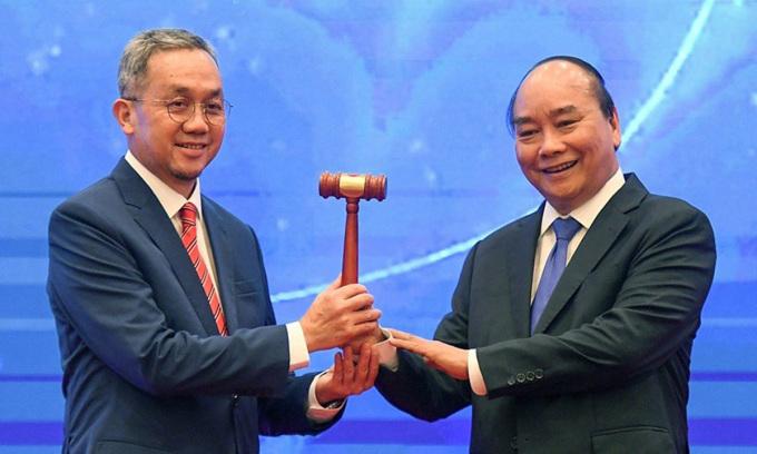 Đại sứ Brunei (trái) tiếp nhận búa Chủ tịch ASEAN từ Thủ tướng Nguyễn Xuân Phúc. Ảnh: Giang Huy.